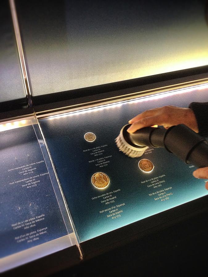 Limpiando bandejas de la Exposición Monedas del MARQ